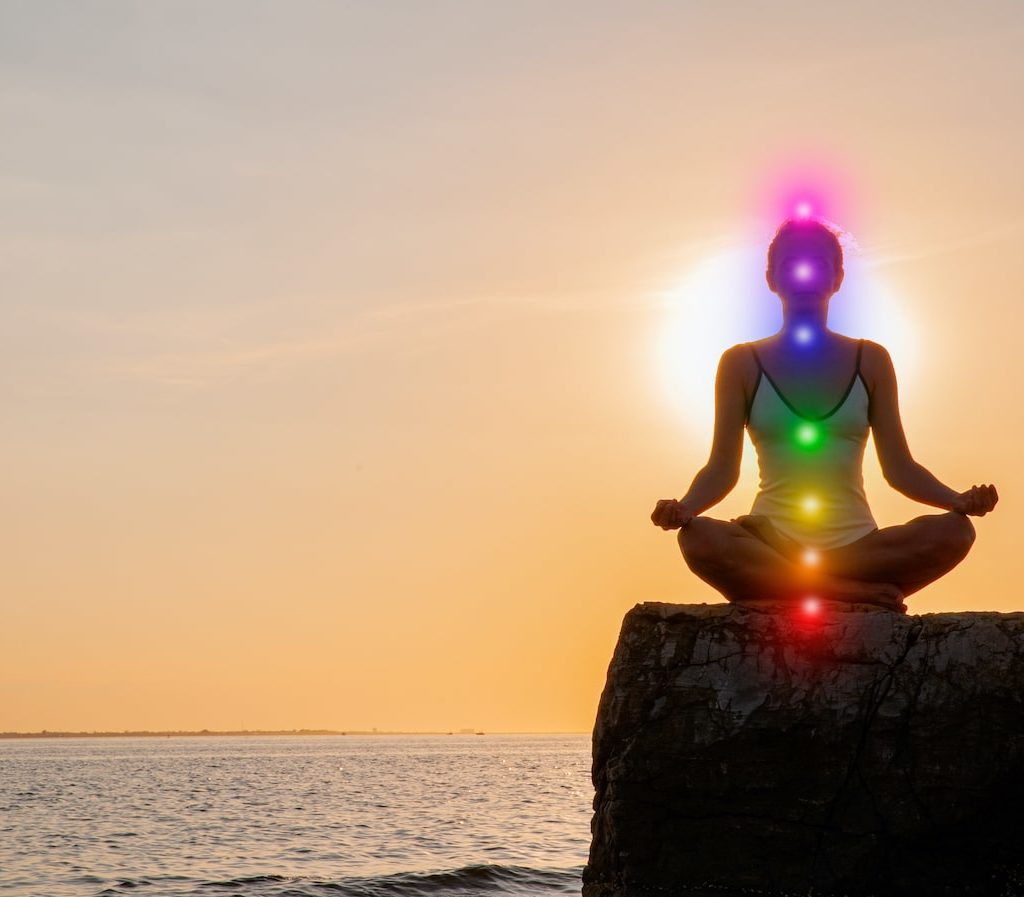 junge Frau sitzt auf einem Felsen und macht eine Chakra Meditation der 7 sieben Chakren