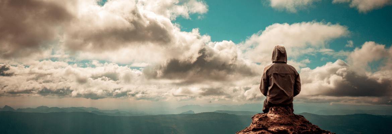 junger Mann sitzt aufgrund von Angst vor Ablehnung alleine auf einem Feld