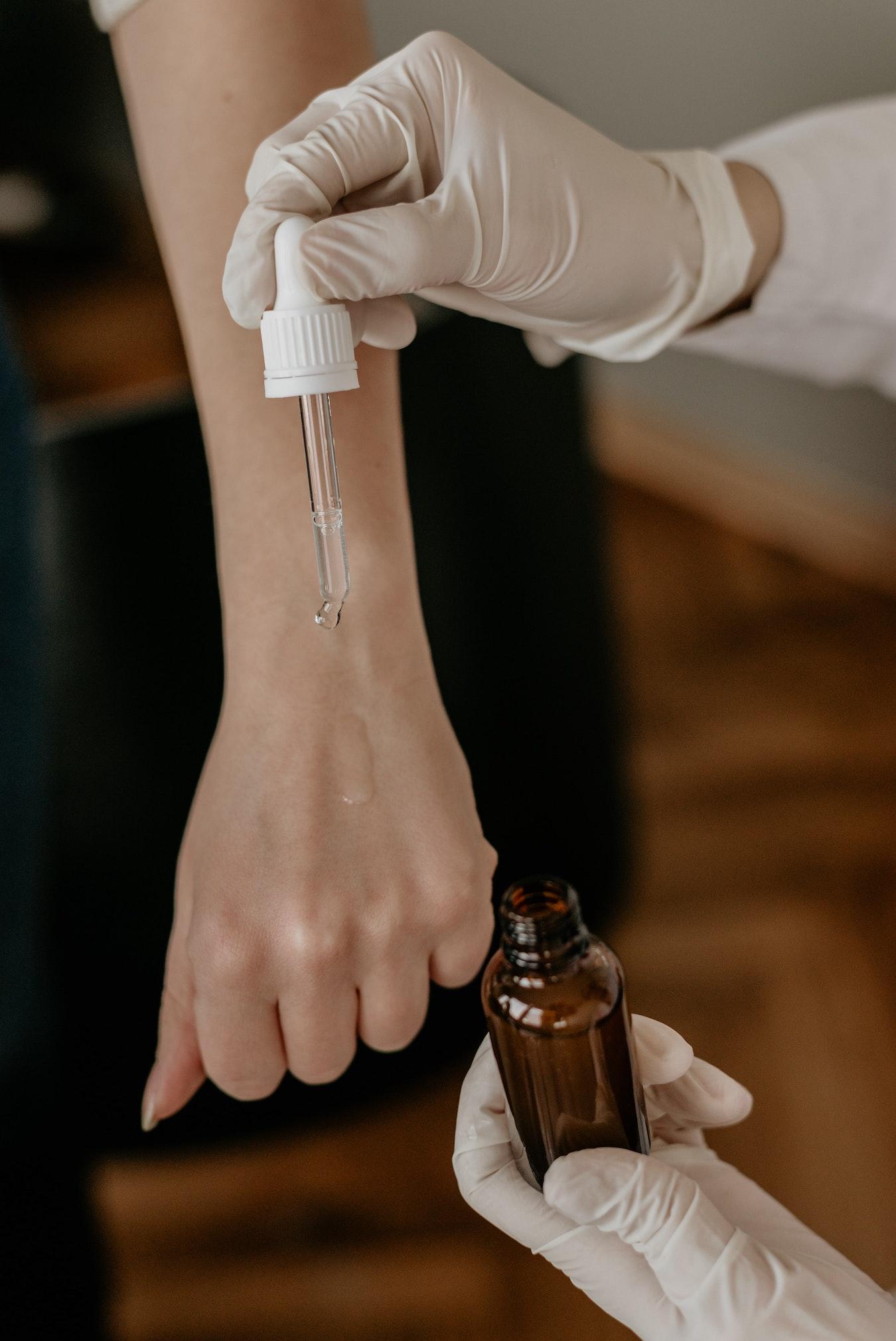 ätherisches Nelkenöl wird mit einer Pipette auf einen Arm getropft Hautpflege mit Öl