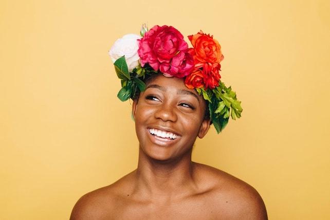 junge Frau mit Blumenkranz auf dem Kopf lächelt und strahlt voller Selbstliebe und Selbstbewusstsein