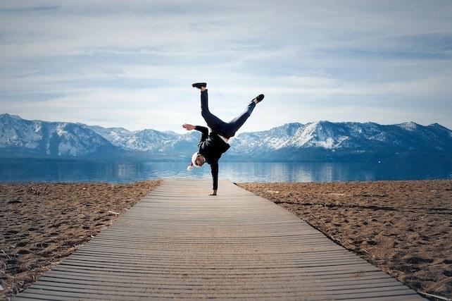 junger Mann macht mit Selbstsicherheit und einer positiven Einstellung einen Handstand vor einem See