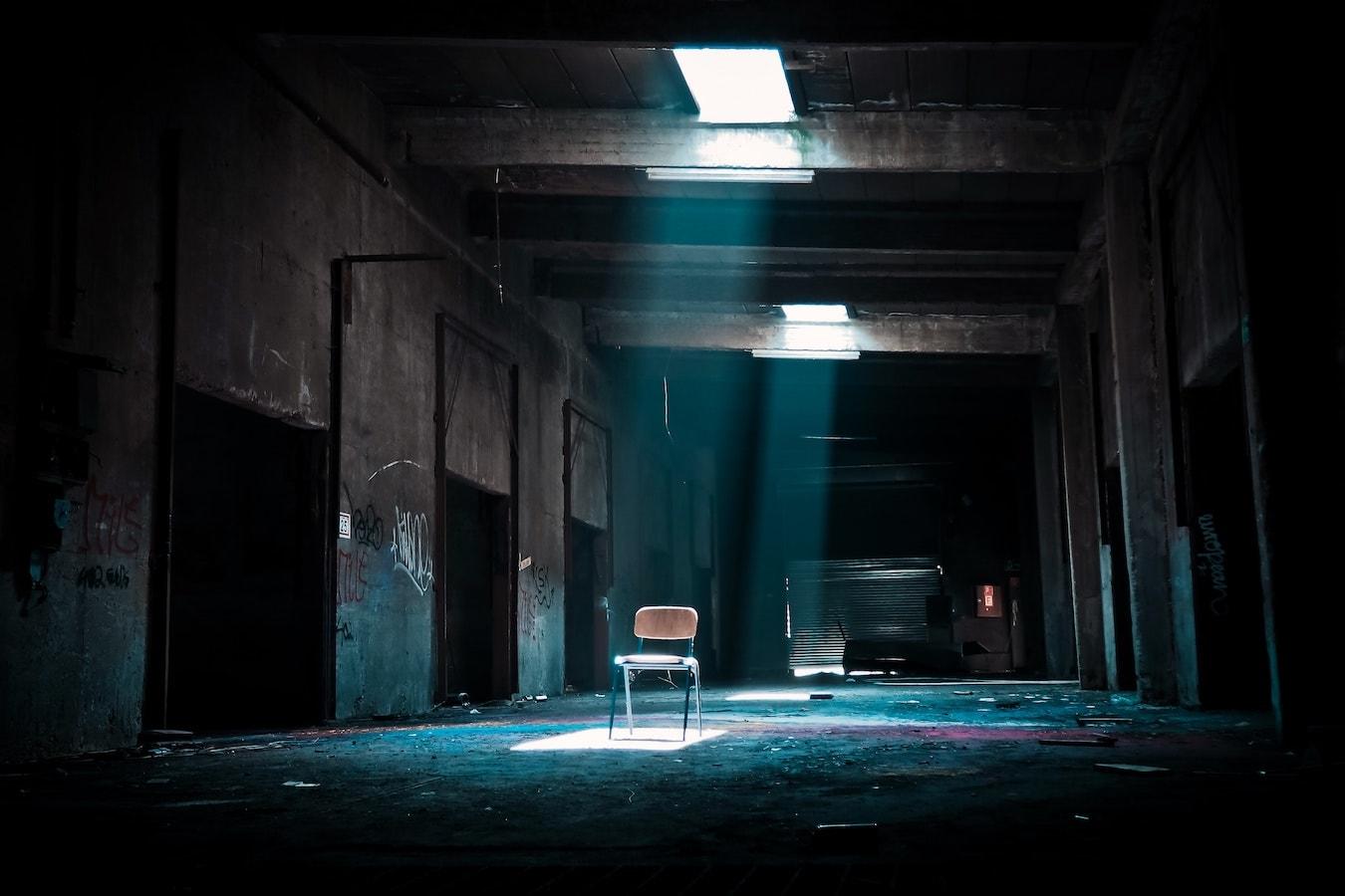 Stuhl in einem leeren dunklen verlassener Raum