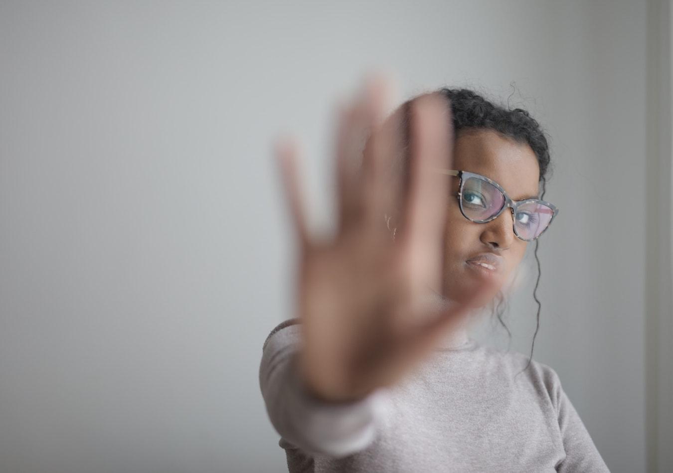 junge Frau hält ihre Handfläche ablehnend vor sie Angst vor Ablehnung