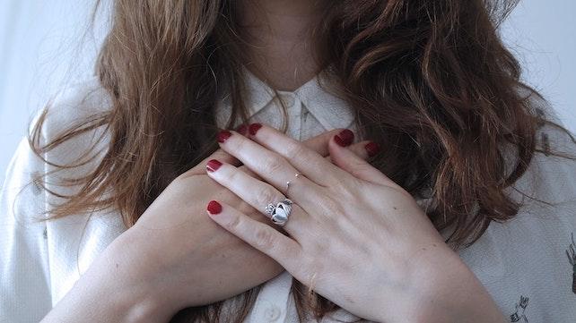 junge Frau hält ihre Hände zusammen vor der Brust für mehr Selbstliebe