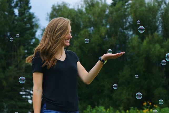 Junge Frau mit positiven Gedanken spielt mit Seifenblasen und ist glücklich