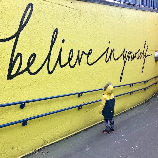kleines Kind steht vor einer gelben Wand mit der Aufschrift believe in yourself - englisch für glaube an dich selbst