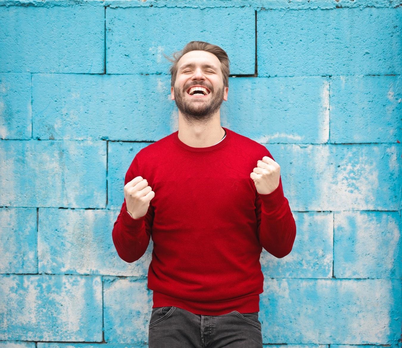 junger Mann im roten Pullover lächelt selbstsicher und selbstbewusst