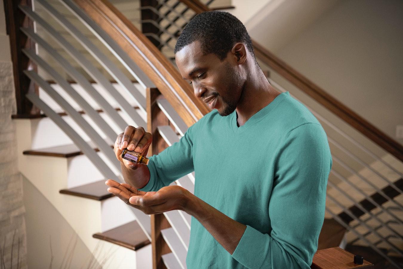 junger Mann tropft ätherisches Nelkenöl mit einer Pipette auf seine Hand