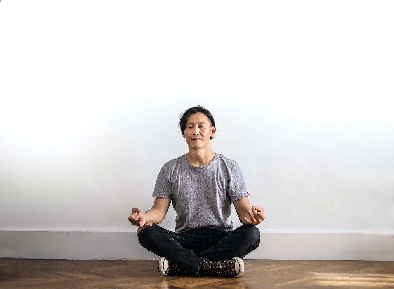 junger Mann meditiert vor einer weißen Wand um seine Selbstzweifel zu überwinden
