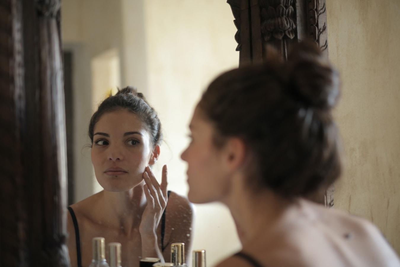 junge Frau schaut sich im Spiegel an und betreibt Hautpflege mit Nelkenöl