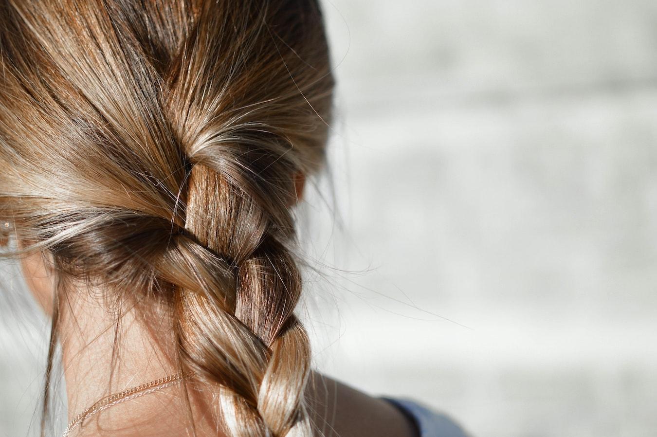 junge Frau mit starken dicken Haaren in einen blonden Zopf gebunden