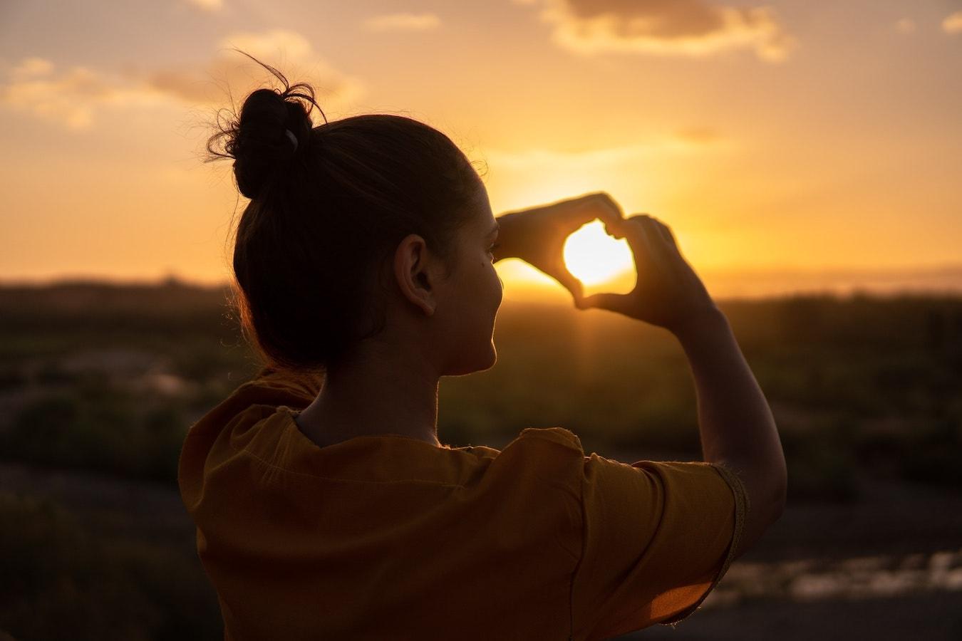 junge Frau hält ihre Hände in Herzform selbstbewusst vor die Sonne