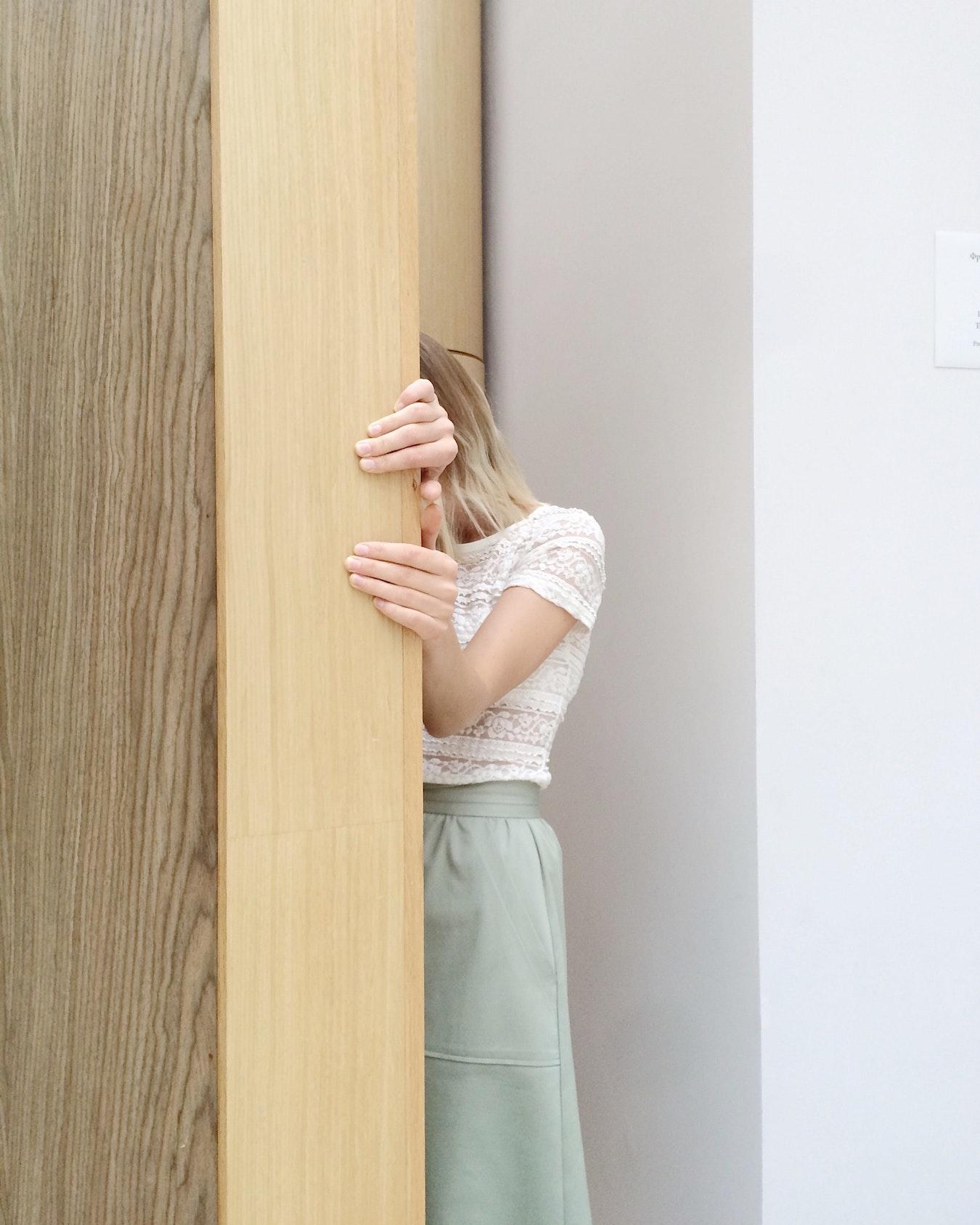 junge Frau versteckt sich hinter einer Tür aus Angst vor Ablehnung