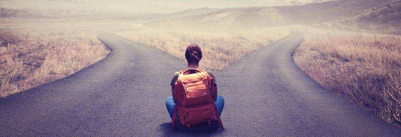 """junge Frau sitzt auf der Straße zwischen zwei Wegen und denkt sich """"ich kann mich nicht entscheiden"""""""