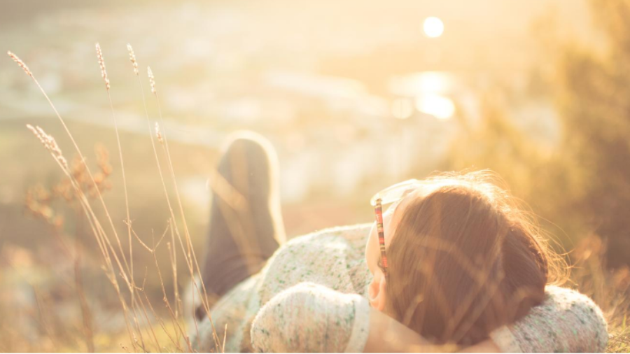 junge Person liegt entspannt und sorgenfrei im Gras und schaut in die Sonne