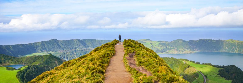 Selbstsabotage überwinden: junger Mann steht auf einem Hügel und genießt