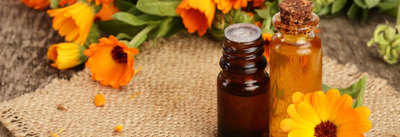 Ringelblumenöl Calendulaöl Fläschchen und Blüten der Ringelblume
