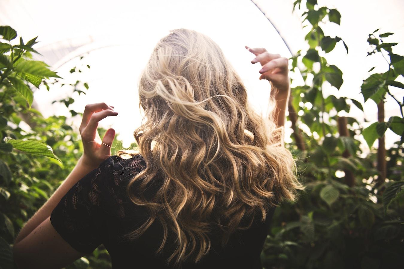 junge Frau mit blonden welligen Haaren gepflegte Haare mit Bergamotteöl