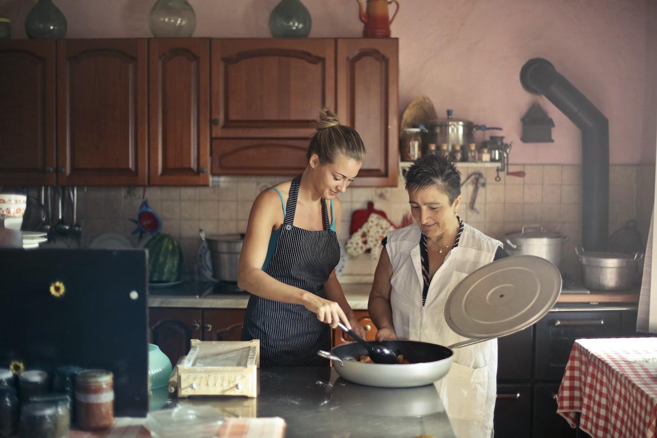 junge Frau und ältere Frau in der Küche kochen zusammen mit Bergamotteöl