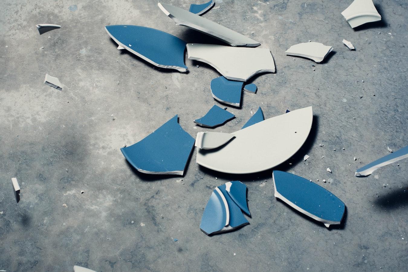 kaputter zerbrochener blauer Teller auf dem Boden - Selbstsabotage Sabotage Niederlage Fail