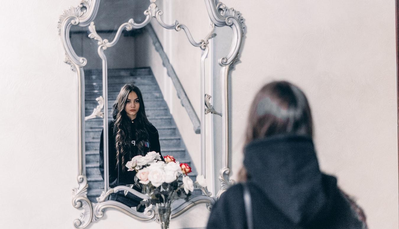 junge Frau schaut in den Spiegel leidet an Selbstsabotage und Manipulation
