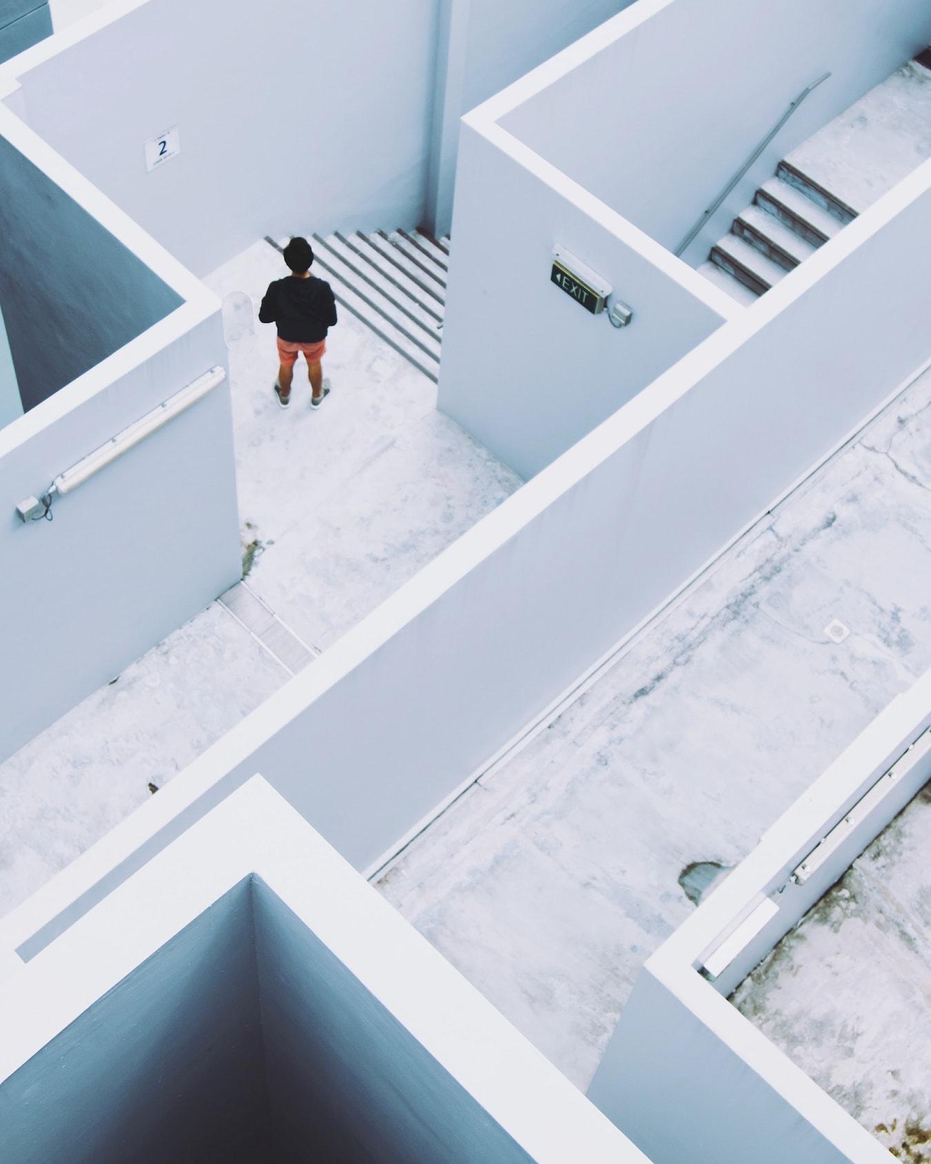 junger Mann findet verzweifelt den Weg aus einem Treppen Labyrinth