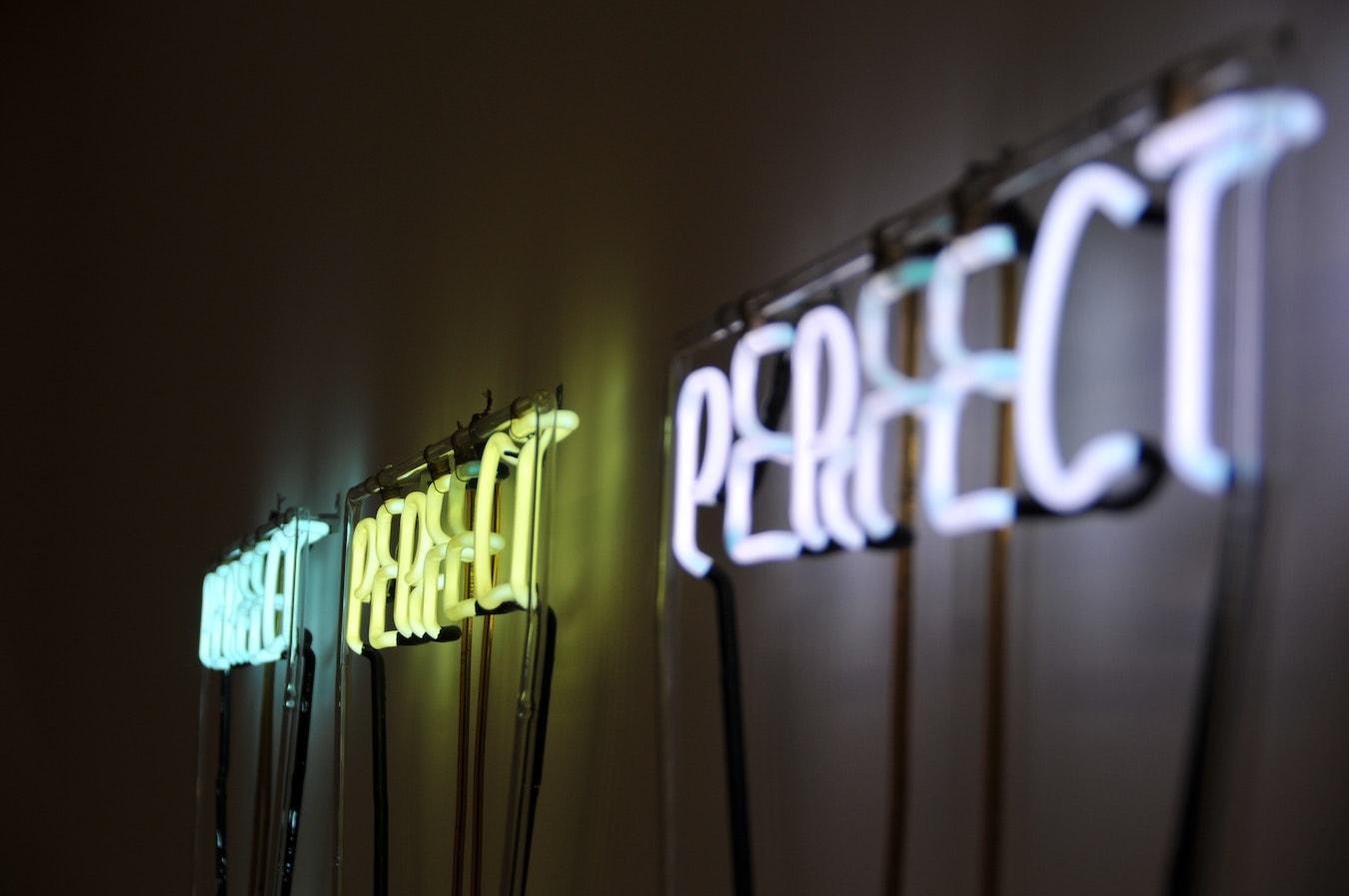 Perfect, perfekt, perfekt leuchtende Aufschrift an der Wand Perfektionismus