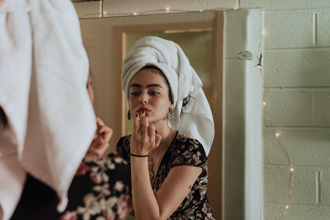 junge Frau behandelt ihre Gesichtshaut mit Calendulaöl Spiegelbild