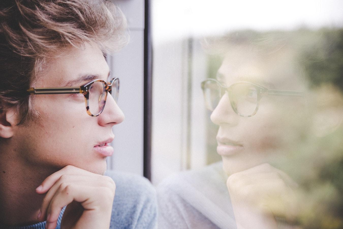 junger Mann schaut sein Spiegelbild im Fenster an und denkt nach