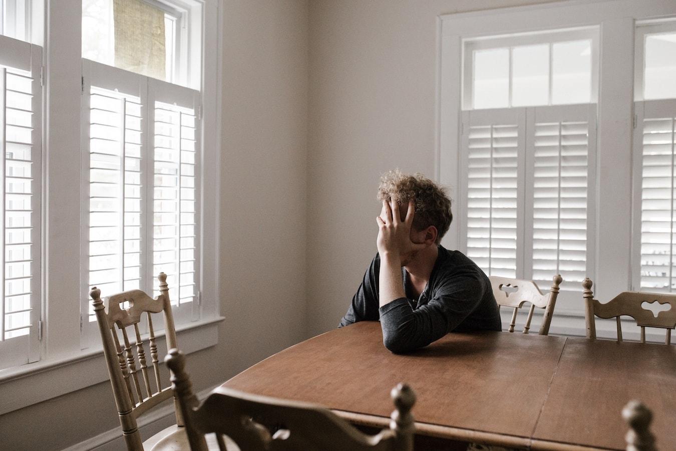 Junger Mann sitzt nachdenklich am Tisch Selbstsabotage Angstzustände Stress
