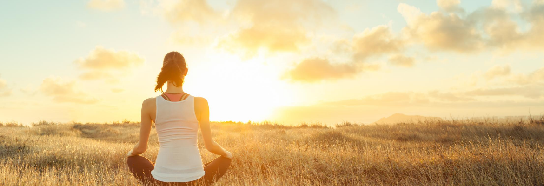 junge Frau meditiert auf einem Feld beim Sonnenuntergang um negative Gedanken loszuwerden