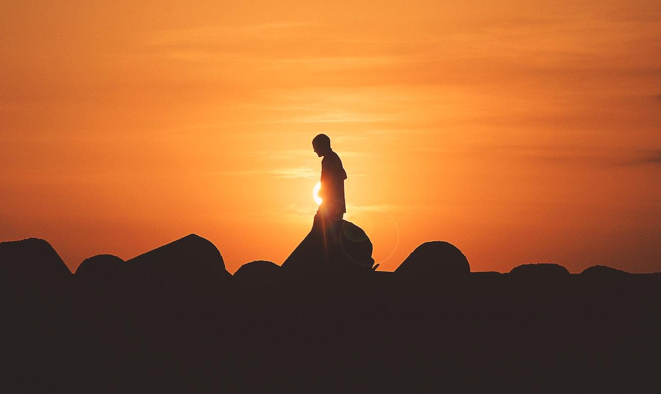 Schatten eines jungen Menschen mit sich selbst beschäftigt vor dem gelben Sonnenuntergang