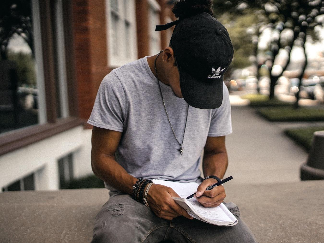 junger Mann sitzt und schriebt Tagebuch