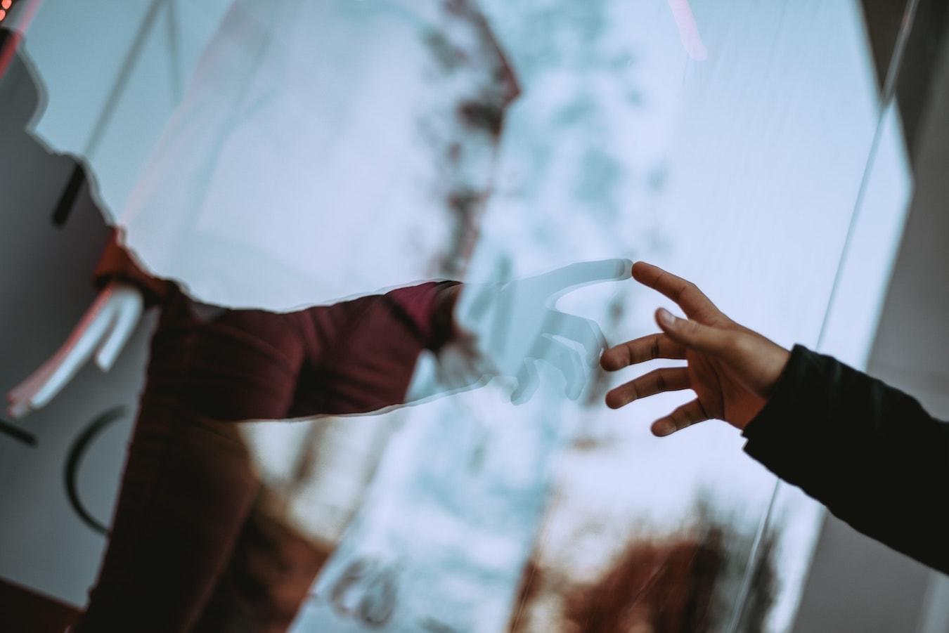 Spiegelbild einer Hand im Fenster: Mit dem höheren Bewusstsein verbinden