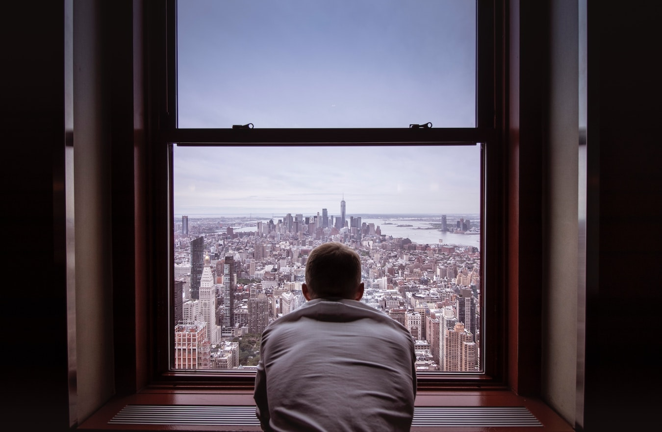junger Mann schaut aus dem Fenster um seine negativen Gedanken loszuwerden