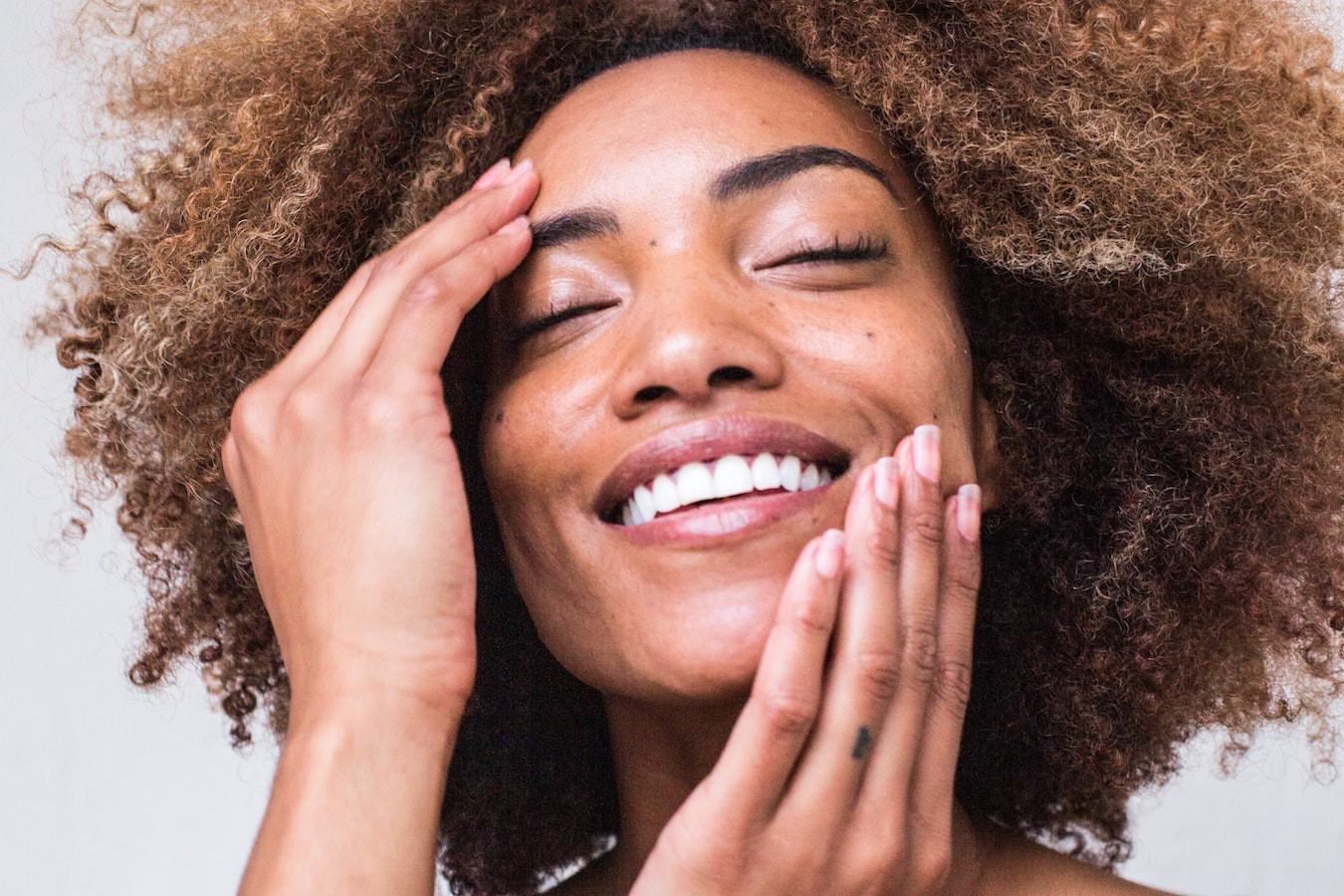 Frau lächelt und streicht sich mit ihren Händen über ihre Gesichtshaut Hautpflege mit ätherischen Ölen