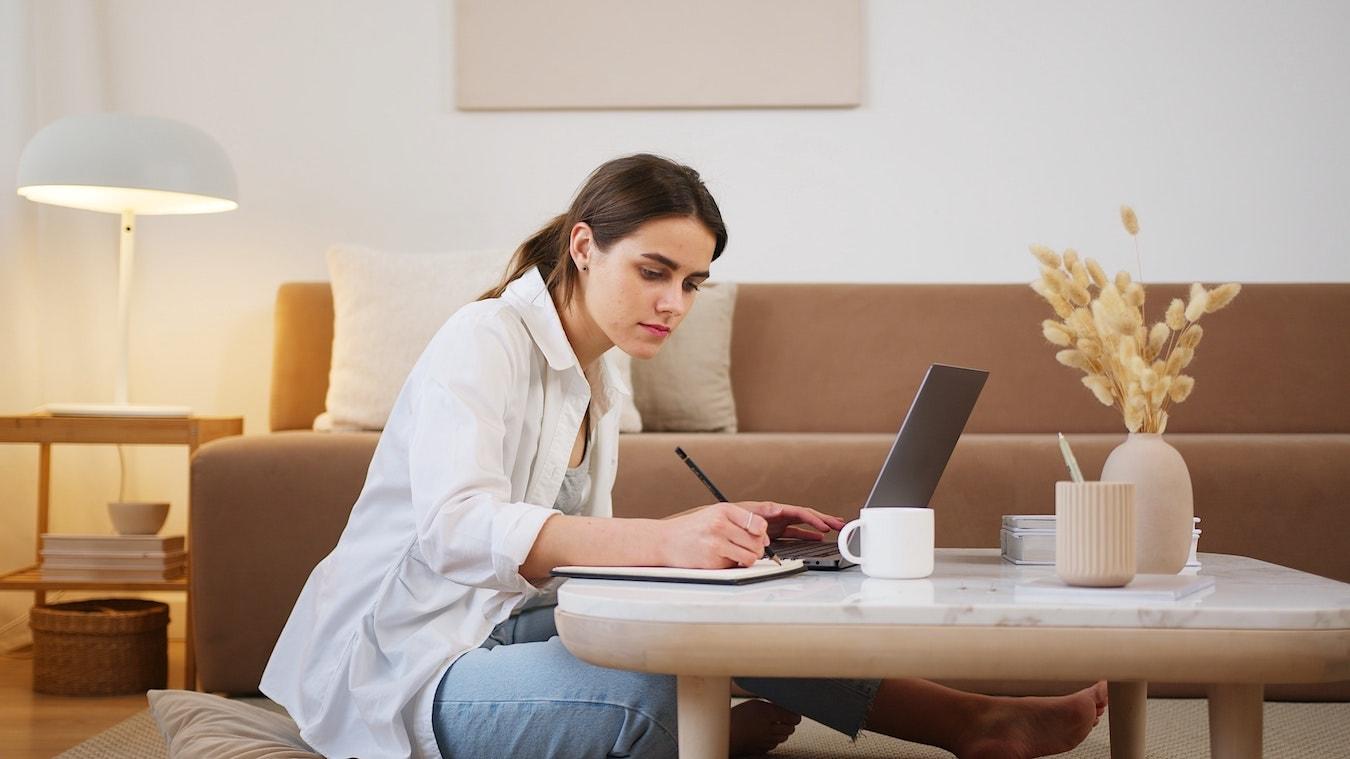 junge Frau sitzt am Schreibtisch mit ihrem Laptop und macht Notizen für ihre Hypnose Ausbildung Coaching
