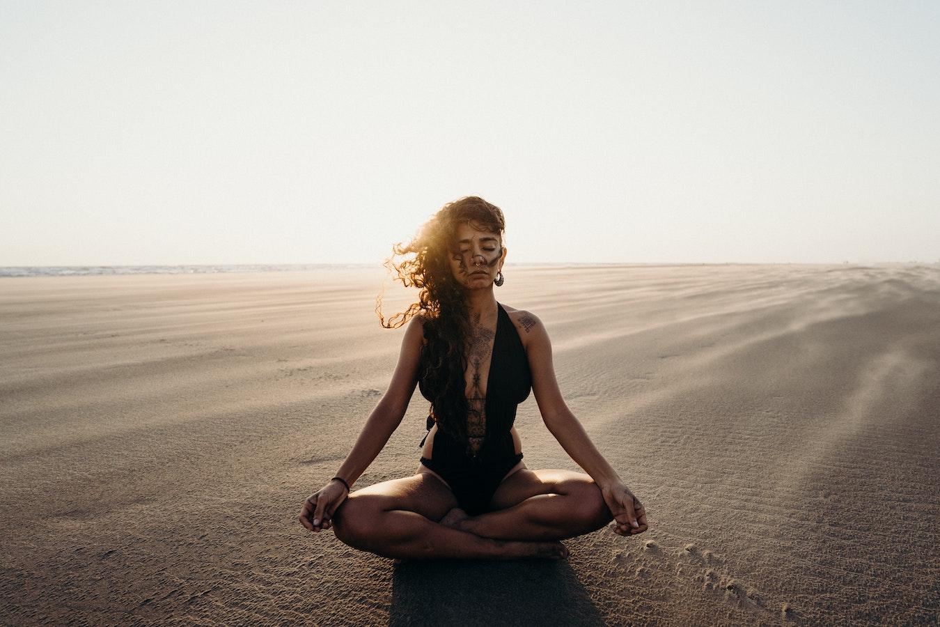 junge Frau im schwarzen Badeanzug sitzt alleine in der Wüste auf dem Sand und verbindet sich mit ihrem höheren selbst durch Meditation