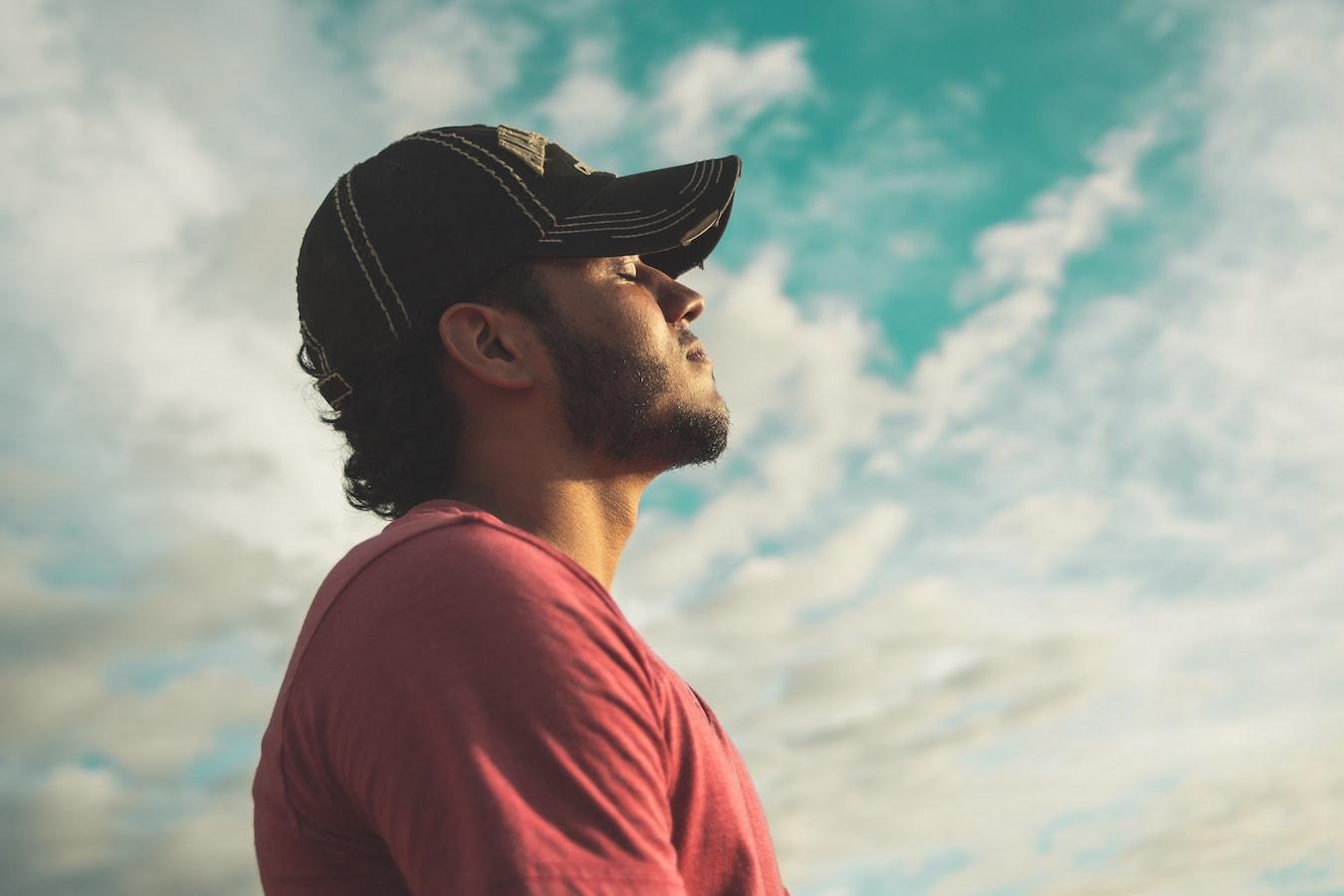 junger Mann mit Cap schaut nachdenklich in den Himmel und will seine negativen Gedanken loswerden