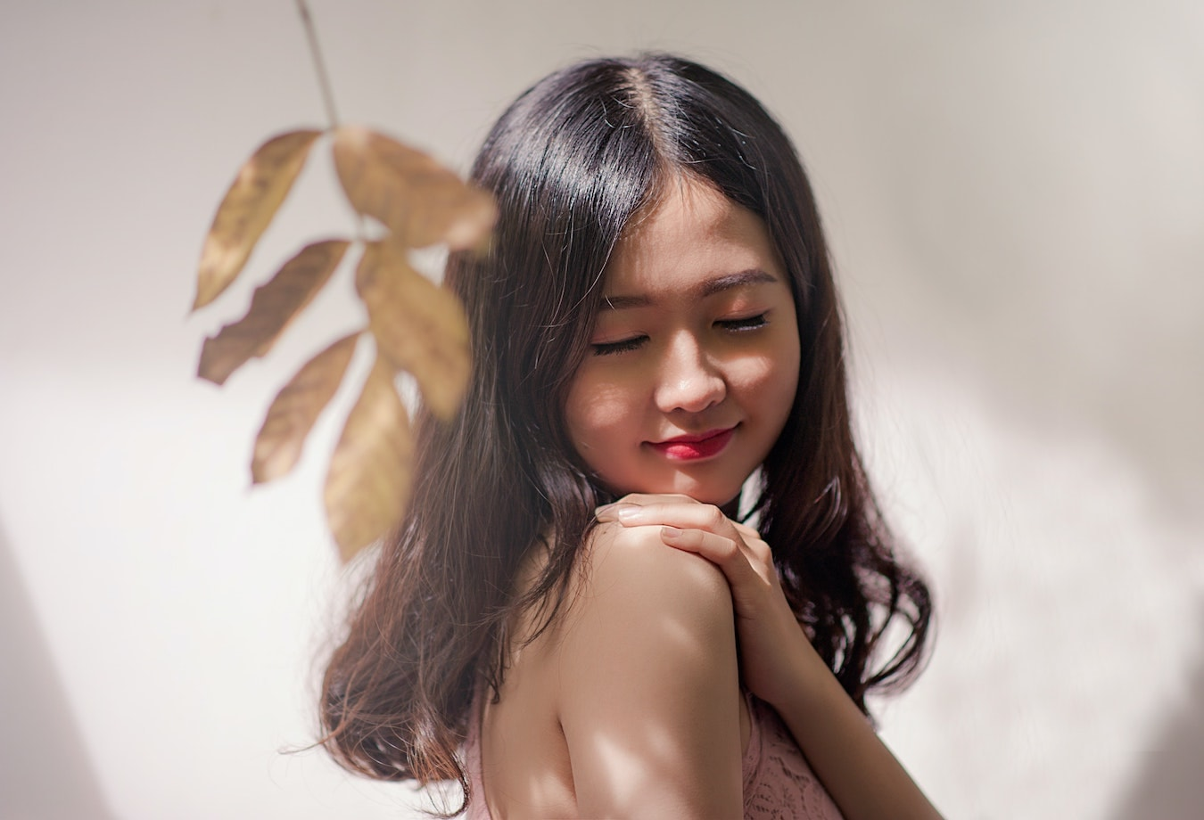 junge asiatische Frau streicht sich über die Haut - natürliche Hautpflege, ätherische Öle für die Haut