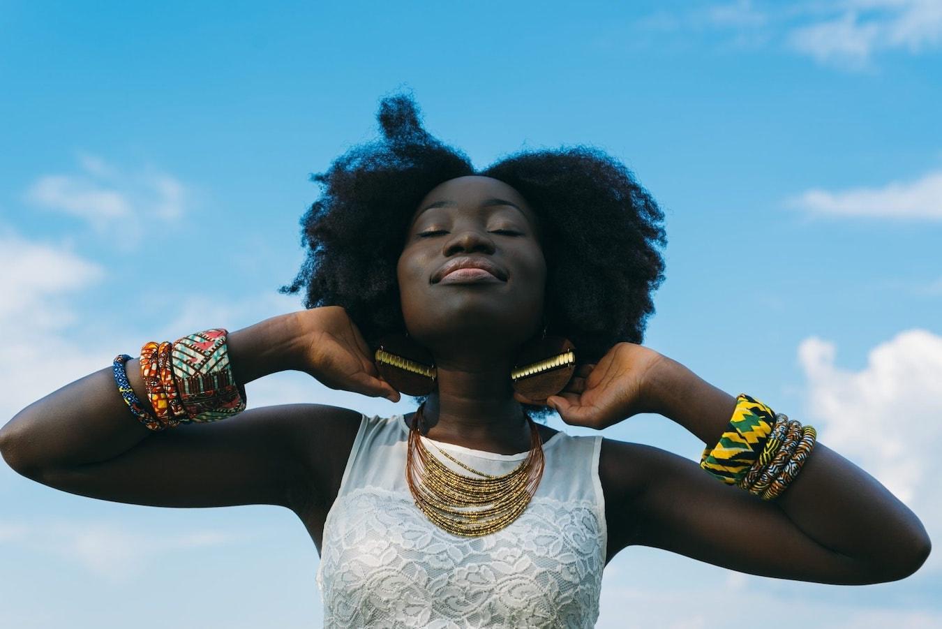 junge dunkelhäutige Frau ist befreit von negativen Gedanken, ist erleichtert, genießt den Moment