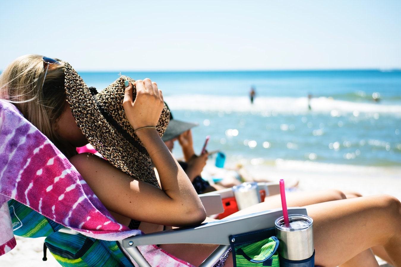 junge Frau am Strand sonnt sich in der Prallen Sonne Gefahr von Sonnenbrand