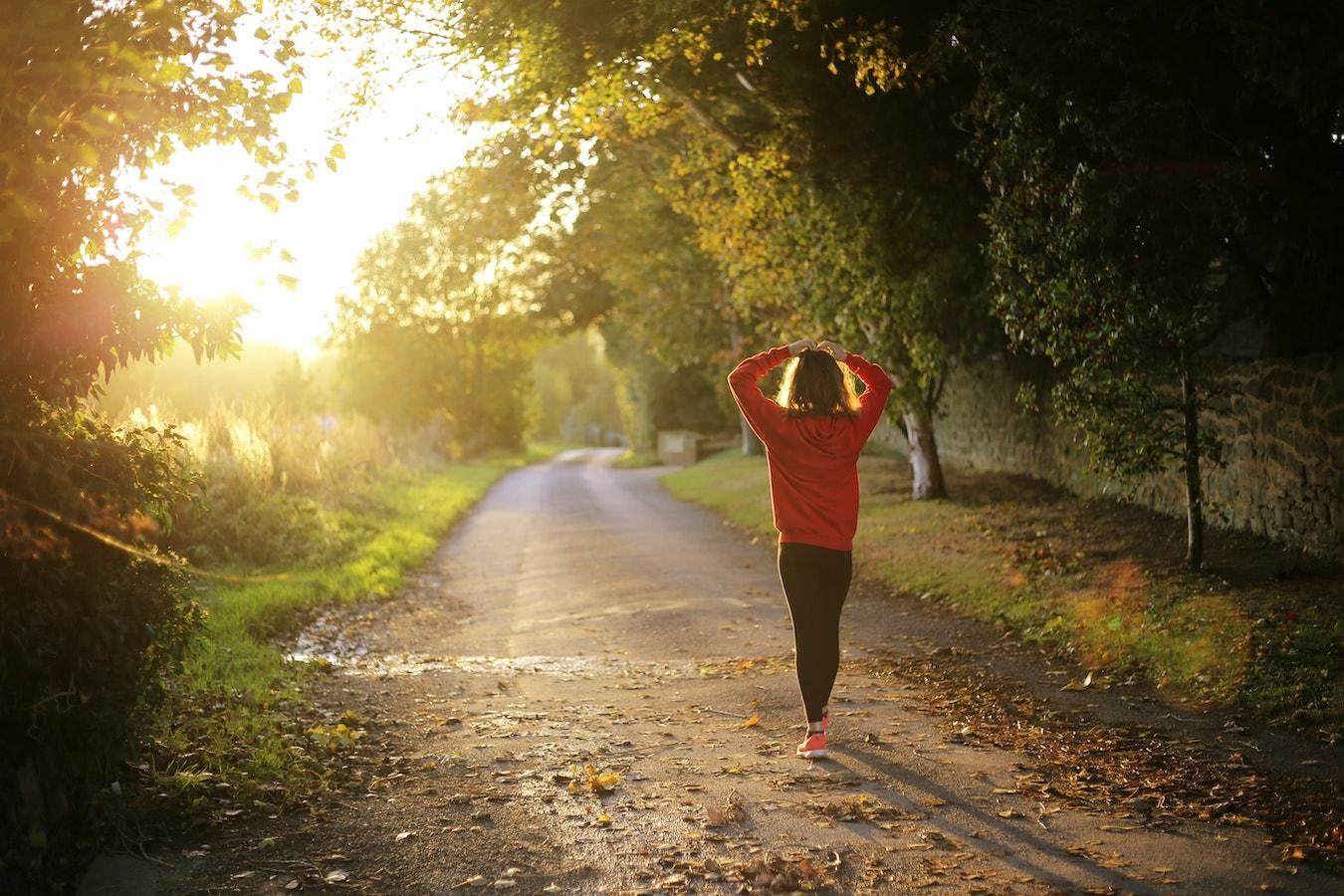 junge Frau läuft durch den Walt und sorgt für Bewegung um Selbstheilungskräfte zu aktivieren