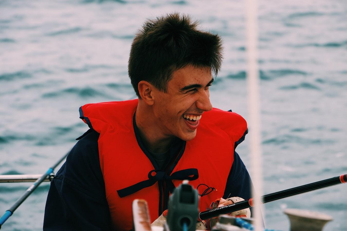 junger Mann lächelt auf einem Boot gute Laune positive Gedanken stärken die Selbstheilung