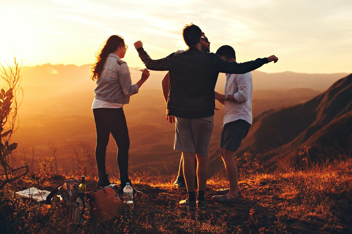 soziale Kontakte und Freundschaften helfen Selbstheilungskräfte zu stärken - eine Gruppe von Freunden sind in der Natur und tanzen