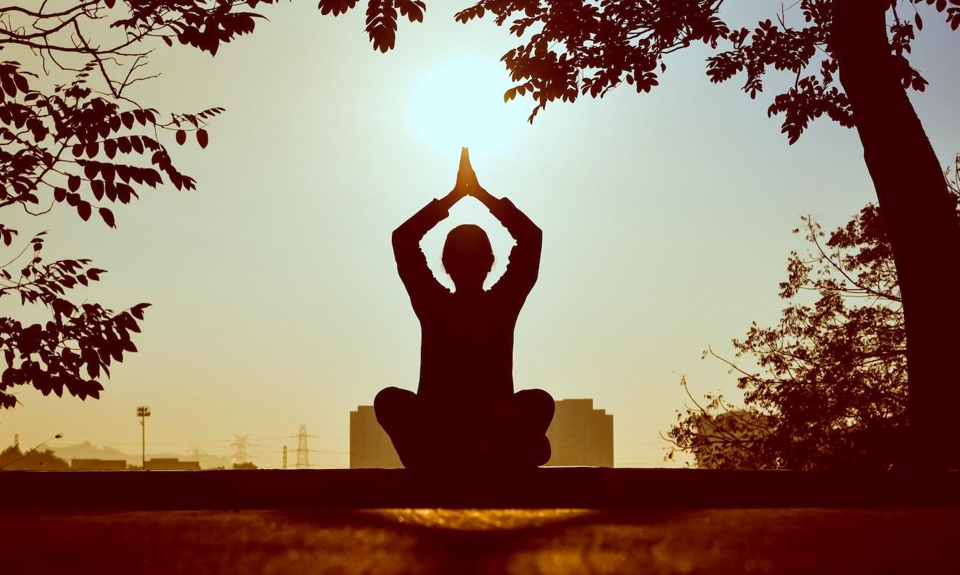 der Schatten einer Person beim Meditieren in der Natur - Meditation unterstützt Selbstheilungskräfte