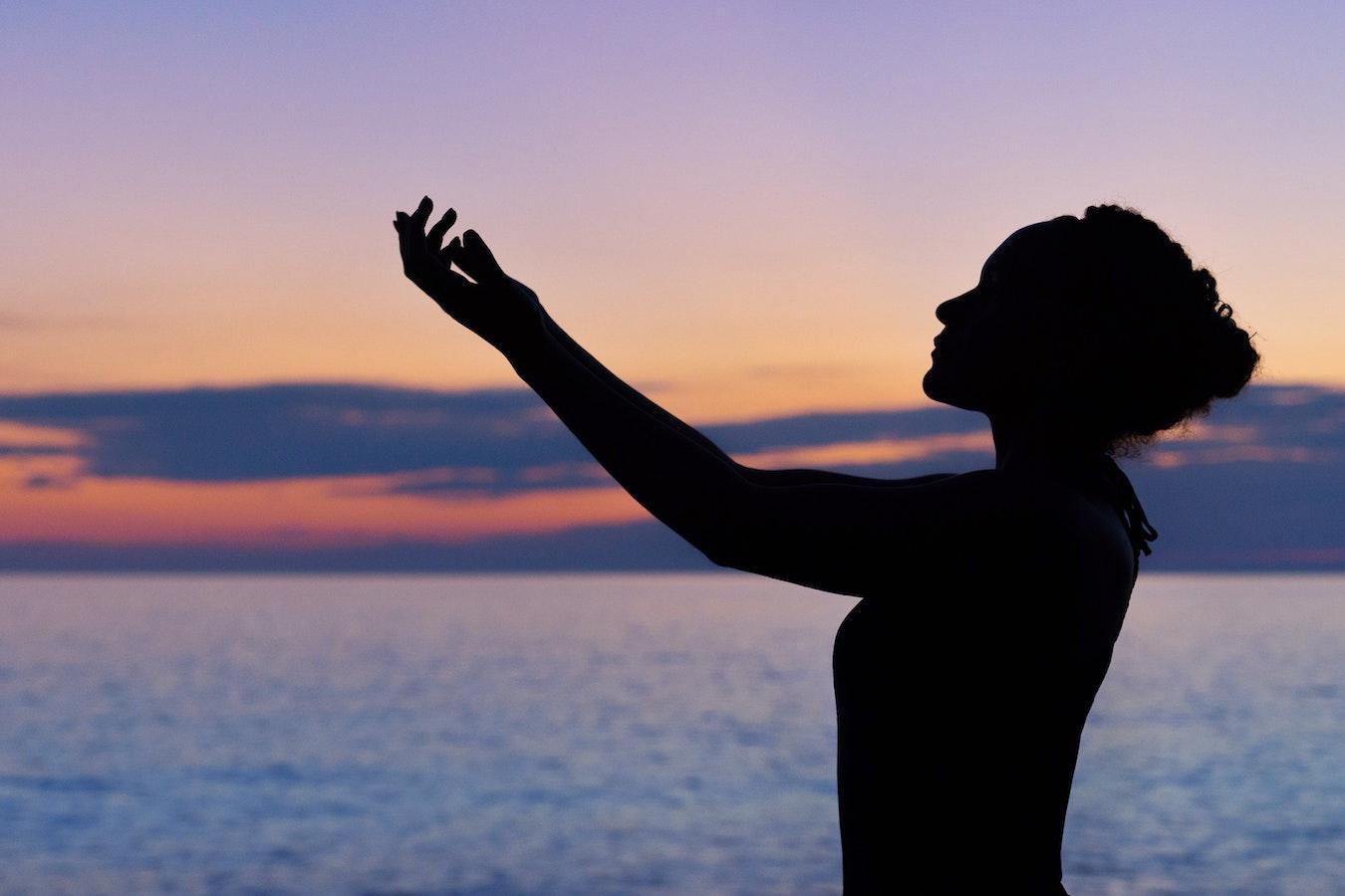 Schatten einer jungen Frau vor dem Sonnenuntergang, die ihre Arme ausstreckt - Energie, Heilung