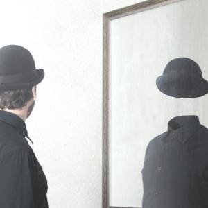 innere Leere - Mann in schwarz mit Hut sieht sich leer im Spiegel