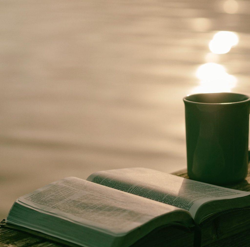 Tasse heißen Kaffee neben einem Buch am Morgen - Morgenroutine hilft beim Faulheit überwinden