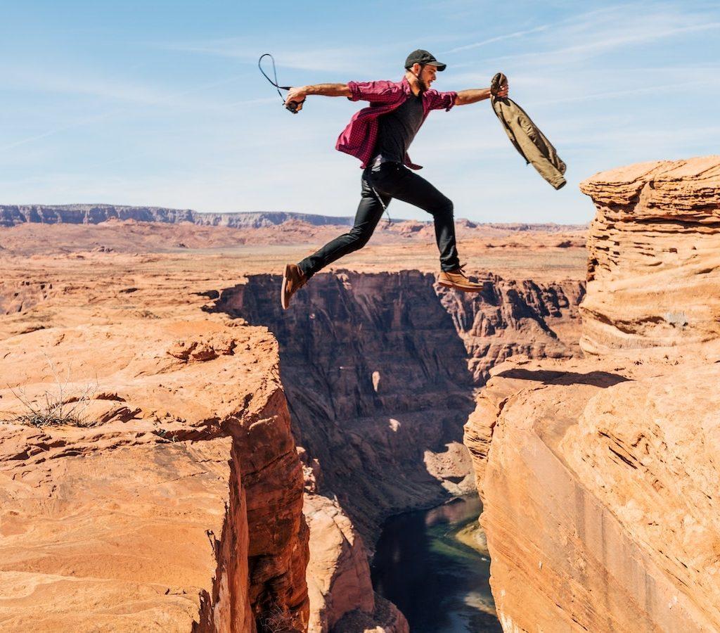 junger Mann springt in der Wüste über einen Graben ist motiviert und produktiv